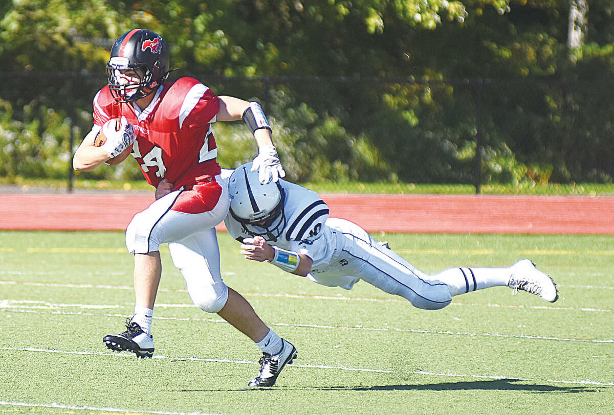 Hour photo/John Nash - Fairfield Warde's Bryan Azarian, left, tries to race away from the diving tackle of Wilton's Matt D'Elisa during Saturday's FCIAC Football game in Fairfield.