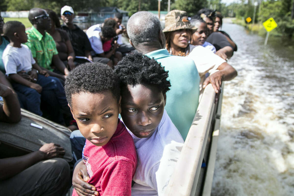 Nasir Linen, 10, holds Tristan Richards, 5, as they ride in the back of a National Guard truck as his family areis evacuated from rising flood waters in the Dunbar Community near Georgetown, S.C., Friday, Oct. 9, 2015. A week after the heavy rains first began, some South Carolina residents are still evacuating and others are stacking up sandbags for more possible flooding even as the nation's top security official prepares to inspect the damage firsthand. (Jason Lee/The Sun News via AP)
