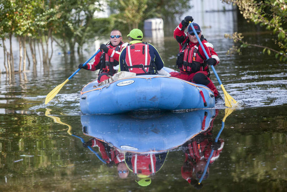 Firefighters evacuate Eliza Linen by boat from her home in the Dunbar Community of Georgetown, S.C., Friday, Oct. 9, 2015. A week after the heavy rains first began, some South Carolina residents are still evacuating and others are stacking up sandbags for more possible flooding even as the nation's top security official prepares to inspect the damage firsthand. /The Sun News via AP)