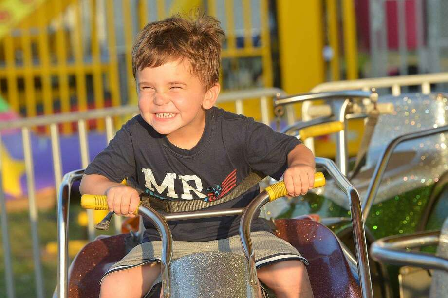 Hour Photo/Alex von Kleydorff 3 yr old Wylen Sparacino gets his go faster face on while riding the race car ride at The Norwalk Seaport Association Oyster Festival on Friday night