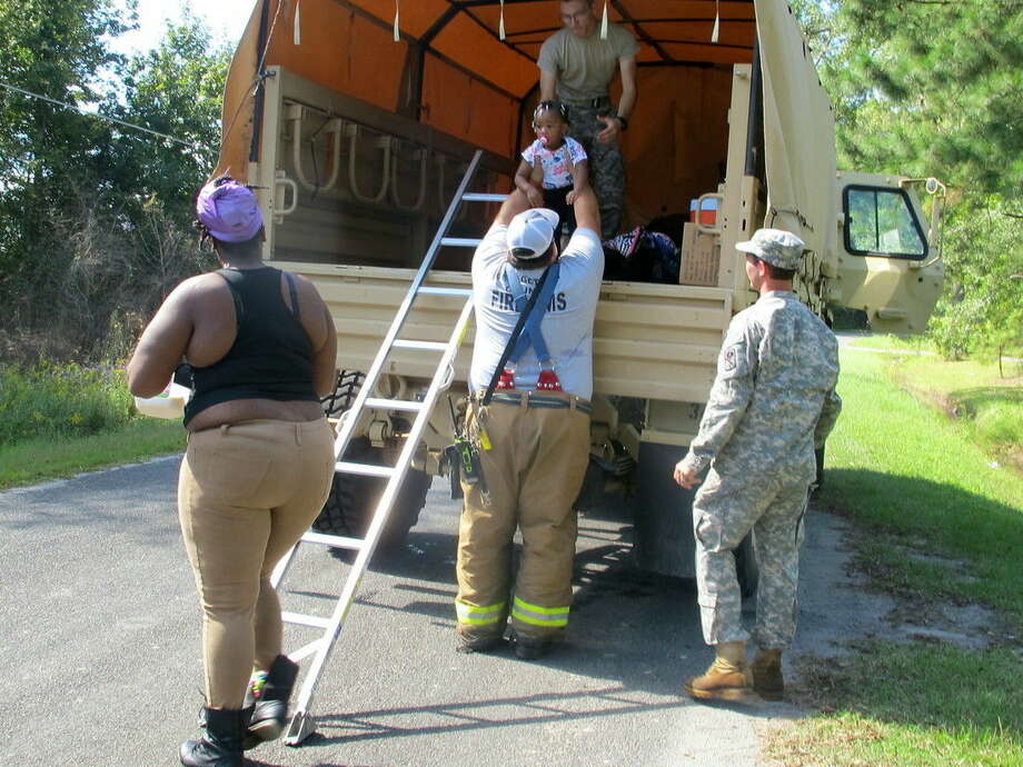 A Georgetown County firefighter helps a child into a South Carolina National Guard truck in Georgetown County, S.C., on Thursday, Oct. 8, 2015. The family was being evacuated as rain-swollen rivers are expected to cause more flooding in the area. (AP Photo/Bruce Smith)