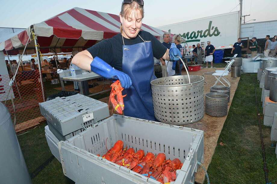Hour Photo/Alex von Kleydorff Exchange Club volunteer Dana Faruolo gets some lobsters ready for the steamer at The Exchange Club tent at The Norwalk Seaport association Oyster Festival on Friday night
