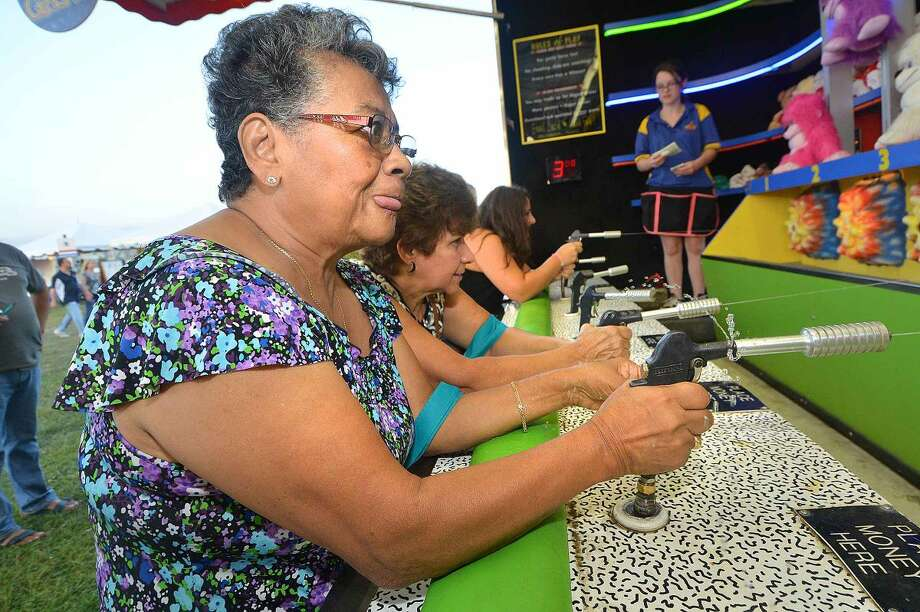 Hour Photo/Alex von Kleydorff Maria Flores and friend Margo Jimenez try for a prize at the water gun booth The Norwalk Seaport association Oyster Festival on Friday night