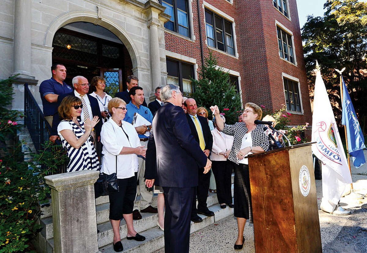 Hour photo / Erik Trautmann Stamford Mayor David Martin and Sister Susan Cunningham, President of The Sisters of St. Joseph Corporation, take part in a presentation of the keys ceremony at the former Sacred Heart Academy which the city purchased Thursday as members of the Planning Board, Board of Finance, Board of Representatives and Board of Education look on.