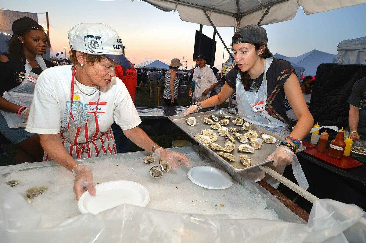 Hour Photo/Alex von Kleydorff Susan Slama and Jonette Colletti get more fresh oysters ready for the crowd at the Flotilla 72 tent at The Norwalk Seaport association Oyster Festival on Friday night