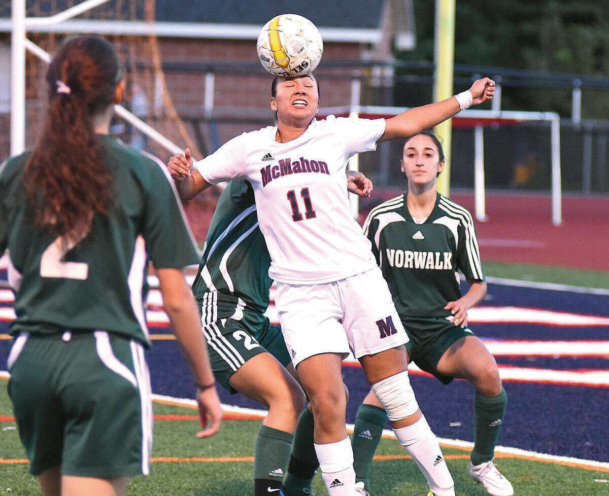Hour photo/John Nash - McMahon's Karissa Ruther (11) heads the ball while being surrounded by a trio of Norwalk players including Melissa Guzman (2) and Caila DeGrandi (right) during Saturday's city rivalry game at Casagrande Field in Norwalk. The two teams battled to 1-1 tie.