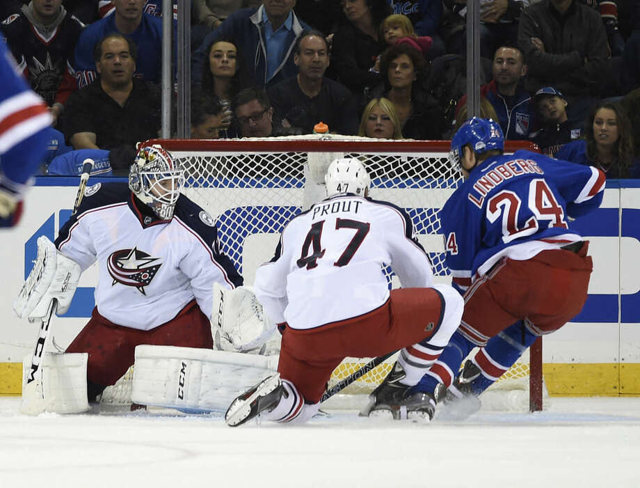 New York Rangers center Oscar Lindberg (24) shoots the puck past Columbus Blue Jackets defenseman Dalton Prout (47) and goalie Sergei Bobrovsky (72) to score his second goal during the first period of an NHL hockey game Saturday, Oct. 10, 2015, in New York. (AP Photo/Kathy Kmonicek)