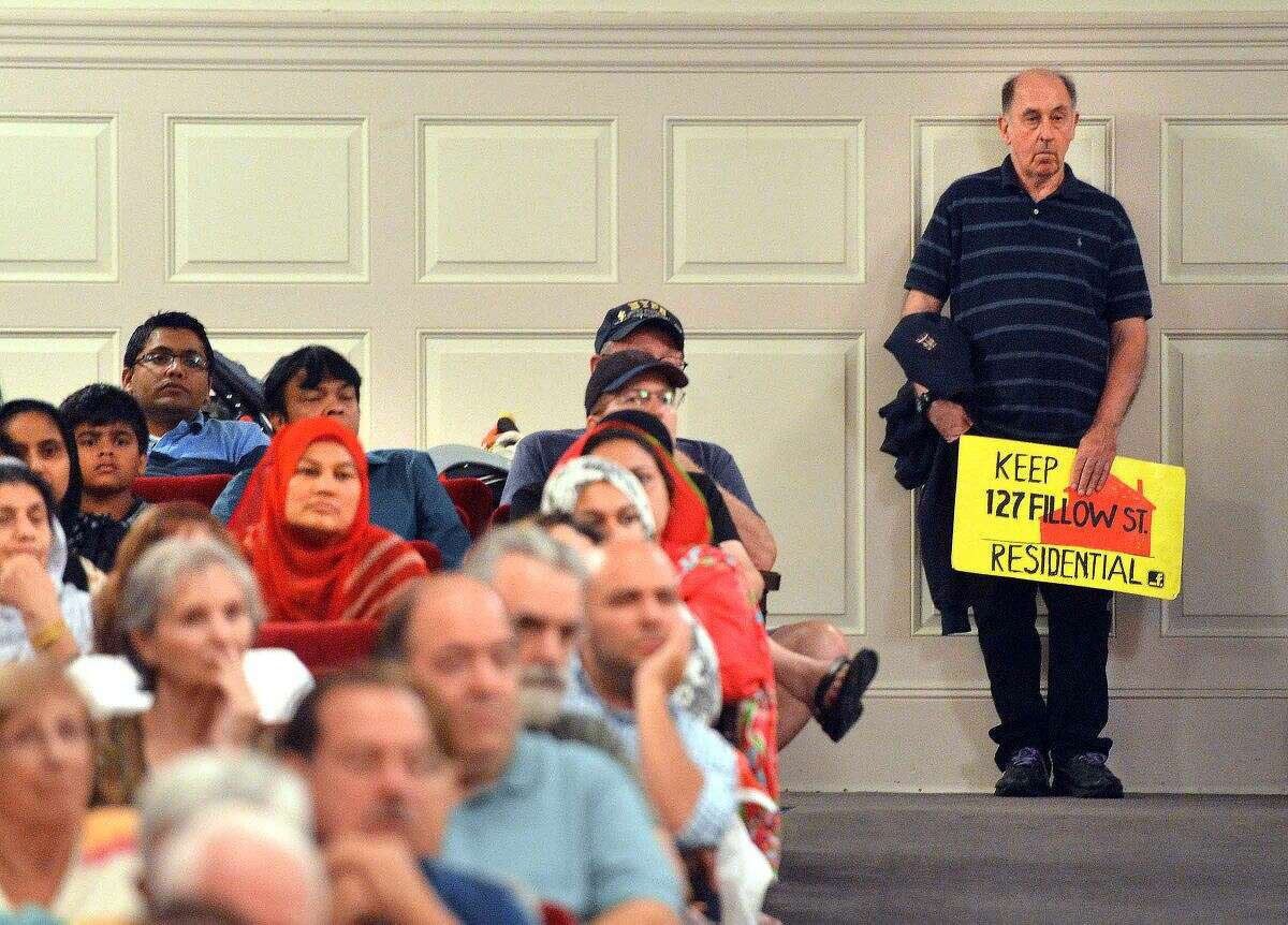 Hour Photo/Alex von Kleydorff A man holds a sign in the back of the Concert Hall during the Norwalk Zoning Commission Public Hearing regarding the proposed Al Madany Islamic Center