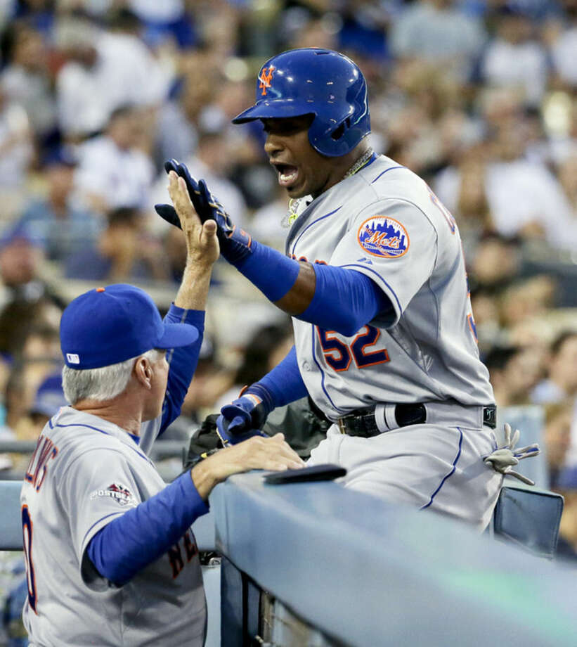 New York Mets' Yoenis Cespedes, right, celebrates his home run with manager Terry Collins during the second inning in Game 2 of baseball's National League Division Series against the Los Angeles Dodgers, Saturday, Oct. 10, 2015 in Los Angeles. (AP Photo/Gregory Bull)