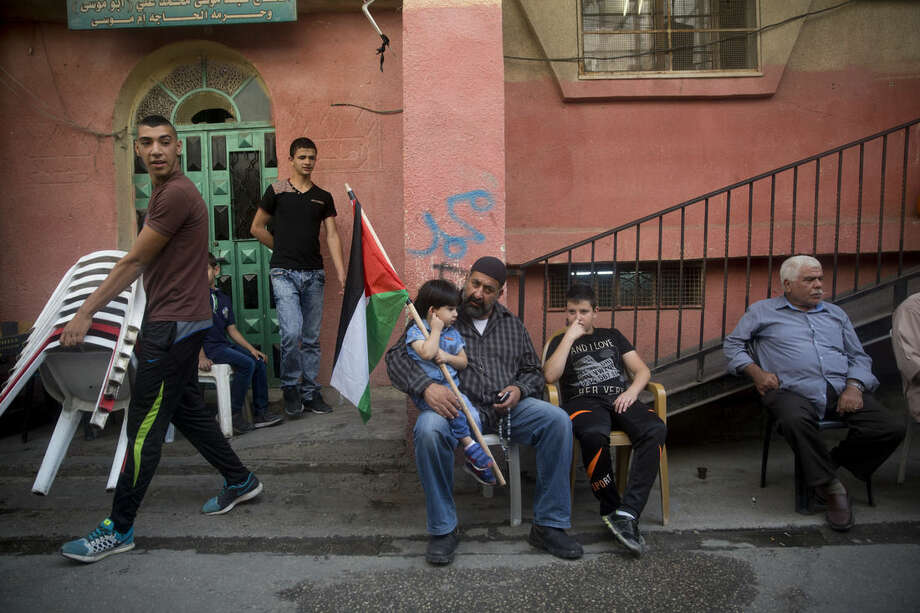 In this Monday, Oct. 12, 2015 photo, a Palestinian boy holds a national flag as he sits on his father's lap outside family home of Mohammed Ali, 19, in Shuafat refugee camp in Jerusalem. Ali was killed after he stabbed an Israeli policeman on Oct. 10 near Old City's Damascus Gate. (AP Photo/Dusan Vranic)