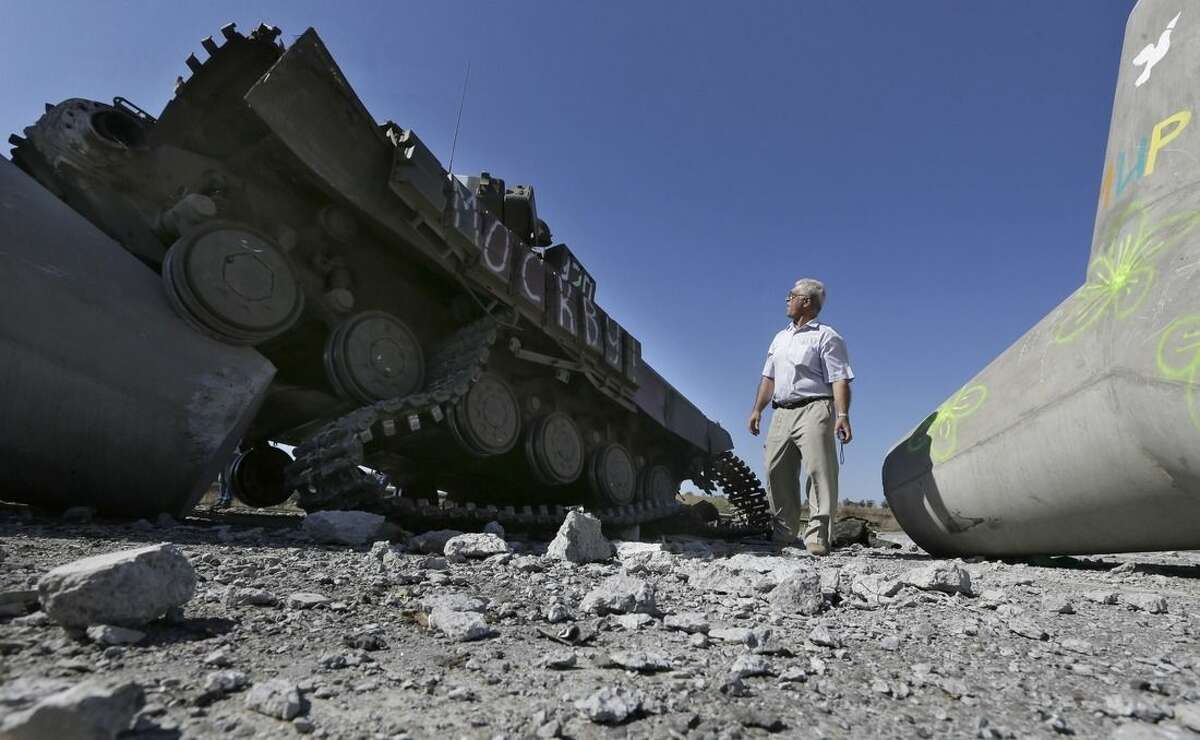 A man looks at a destroyed Ukrainian army tank near the village of Lebedynske, on the highway joining Mariupol and Novoazovsk, Ukraine, Saturday, Sept. 6, 2014. After four months of war, eastern Ukraine begins the first full day of an uncertain cease-fire. The truce agreement calls for an exchange of prisoners and establishment of humanitarian corridors, but how quickly those actions will begin is unclear. (AP Photo/Sergei Grits)