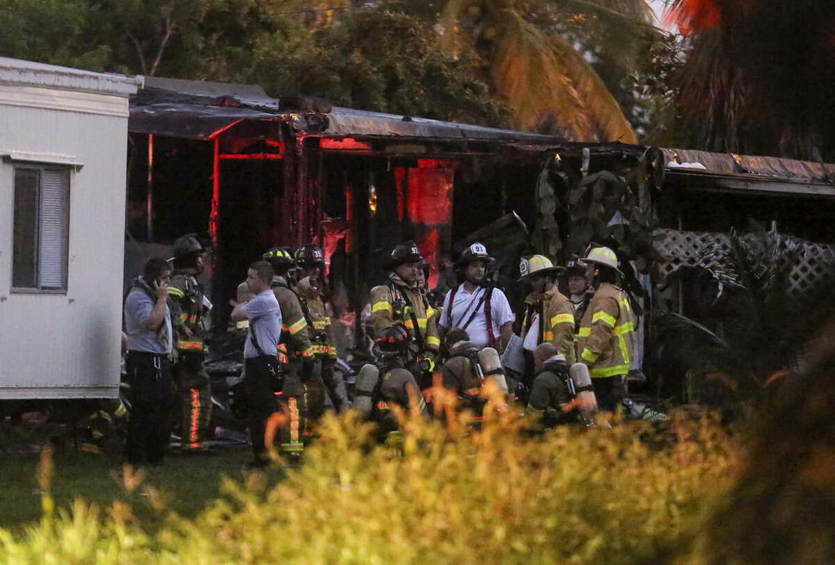 Firefighters gathrt after putting out a blaze caused when a small plane crashed into a mobile home park in Lake Worth, Fla., Tuesday, Oct. 13, 2015. The aircraft hit several homes at the Mar-Mak Colony Club. (Bruce R. Bennett/Palm Beach Post via AP) MAGS OUT; TV OUT; NO SALES; MANDATORY CREDIT