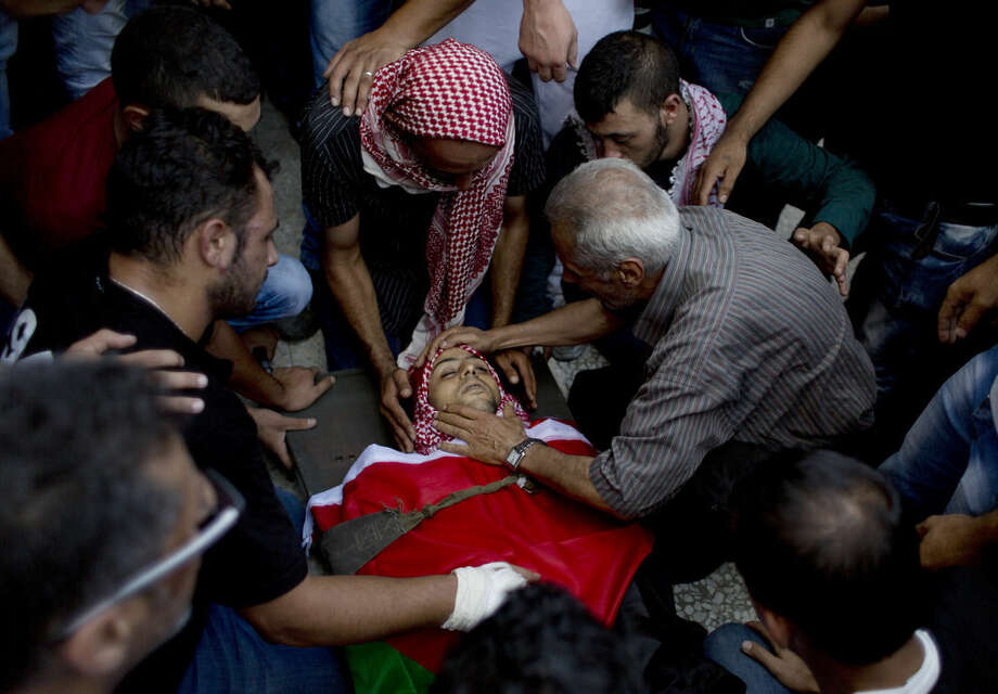 Palestinians take the last look at the body of Moataz Zawahara, who was killed in clashes with Israeli troops, during his funeral in Deheisha refugee camp, near the West Bank city of Bethlehem, Wednesday, Oct. 14, 2015. (AP Photo/Nasser Nasser)