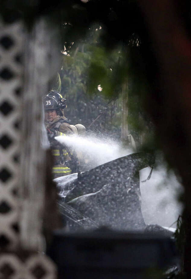 A firefighter spays water on a burning home after a small plane crashed into a mobile home park in Lake Worth, Fla., Tuesday, Oct. 13, 2015. The aircraft hit several homes at the Mar-Mak Colony Club. (Bruce R. Bennett/Palm Beach Post via AP) MAGS OUT; TV OUT; NO SALES; MANDATORY CREDIT