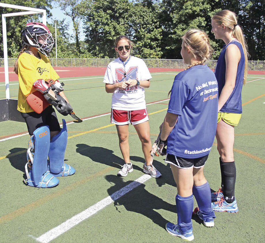 Hour photo/Danielle CallowayBrien McMahon's new field hockey coach, Stephanie Fazio, center, instructs goalie Keara Myerson, Arija Forsyth and Stephanie Mangels during practice last Friday afternoon.