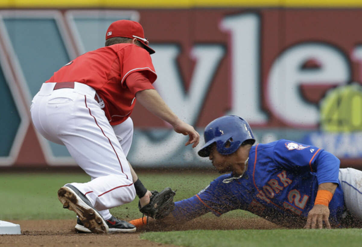 Cincinnati Reds shortstop Zack Cozart, left, tags out New York Mets' Juan Lagares, right, trying to steal second base in the first inning of a baseball game, Saturday, Sept. 6, 2014, in Cincinnati. (AP Photo/Al Behrman)