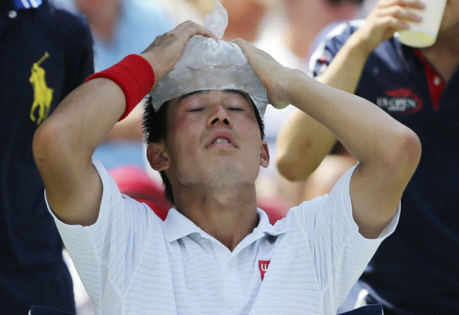 Kei Nishikori, of Japan, puts an ice pack on his head during a break between games against Novak Djokovic, of Serbia, during the semifinals of the 2014 U.S. Open tennis tournament, Saturday, Sept. 6, 2014, in New York. (AP Photo/Mike Groll)
