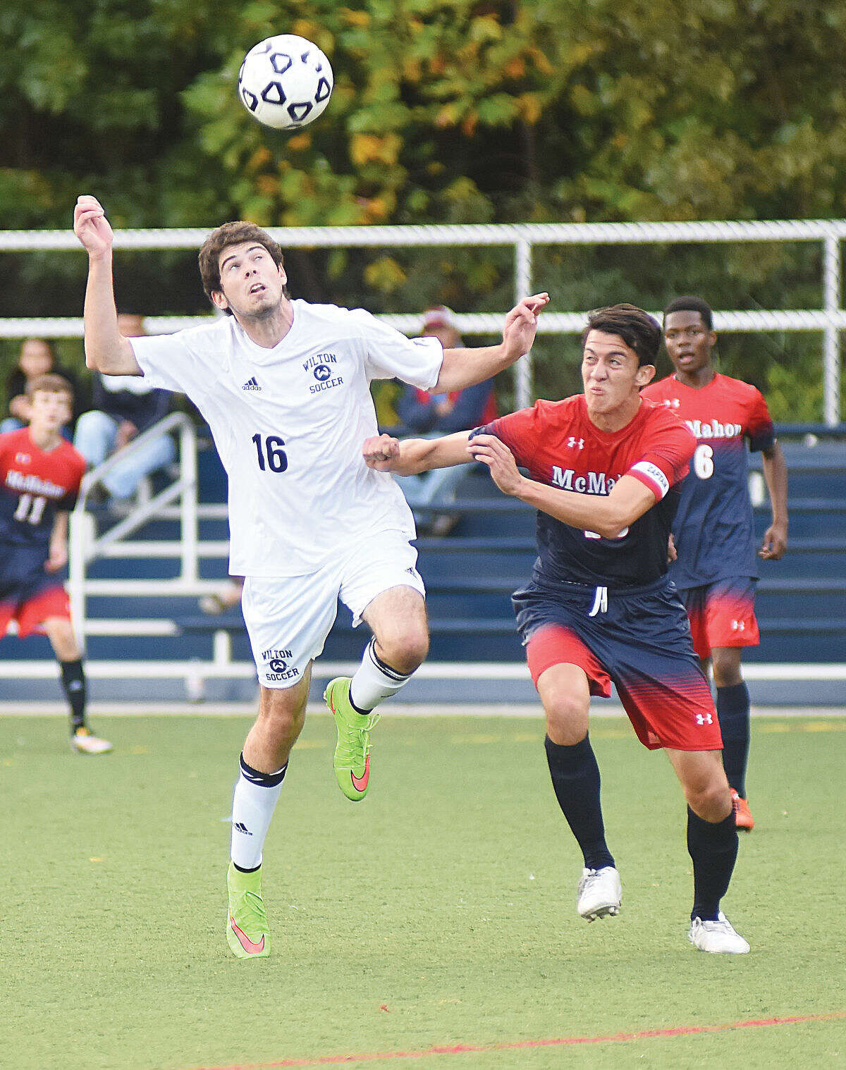 Hour photo/John Nash - Wilton's Bryan Perlee, left, and Brien McMahon's Helmuth Iraheta battle for a ball during Wednesday's FCIAC boys soccer game in Wilton.