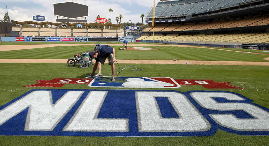 Los Angeles Dodgers grounds crew worker Justin Patenaud paints the National League Division Series logo on the field in preparation for Thursday's game 5 between the Dodgers and the New York Mets in Los Angeles, Wednesday, Oct. 14, 2015. (AP Photo/Alex Gallardo)