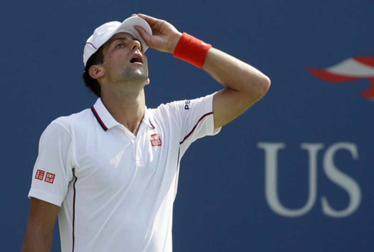 Novak Djokovic, of Serbia, adjusts his cap between points against Kei Nishikori, of Japan, during the semifinals of the 2014 U.S. Open tennis tournament, Saturday, Sept. 6, 2014, in New York. (AP Photo/Darron Cummings)