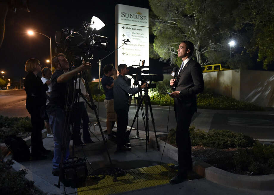 Members of the media stand outside Sunrise Hospital and Medical Center while waiting for word about Lamar Odom on Tuesday, Oct. 13, 2015, in Las Vegas. Odom, a former NBA basketball player, was hospitalized after he was found unconscious at a Nevada brothel, authorities said. (AP Photo/David Becker)