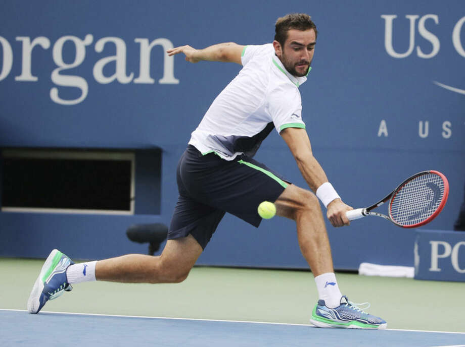 Marin Cilic, of Croatia, returns a shot against Roger Federer, of Switzerland, during the semifinals of the 2014 U.S. Open tennis tournament, Saturday, Sept. 6, 2014, in New York. (AP Photo/Mike Groll)