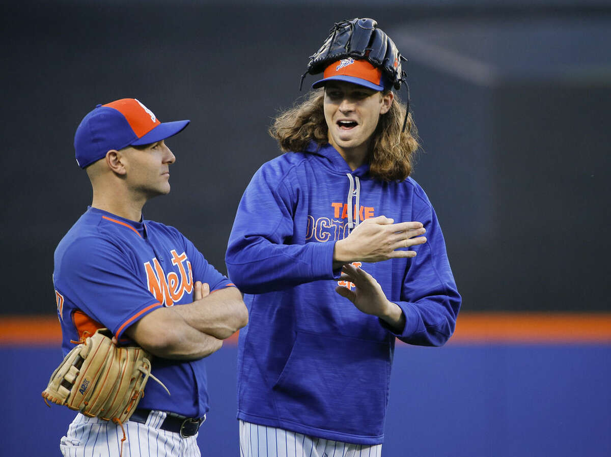 New York Mets bullpen catcher Dave Racaniello, left, and pitcher Jacob DeGrom talk in the outfield during batting practice before the start of baseball's Game 4 of the National League Division Series against the Los Angeles Dodgers, Tuesday, Oct. 13, 2015, in New York. (AP Photo/Kathy Willens)