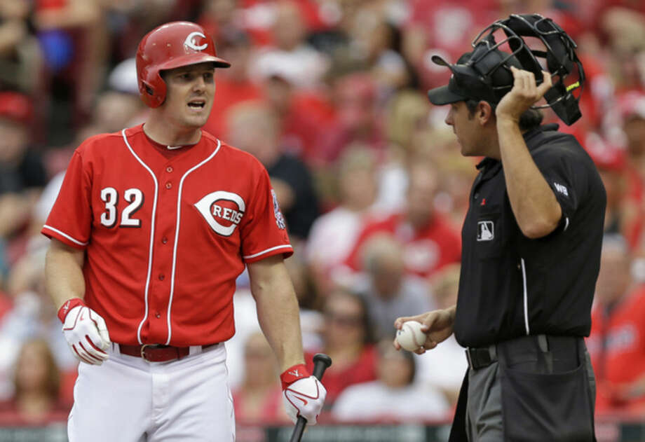 Cincinnati Reds' Jay Bruce (32) argues a called third strike with home plate umpire Mark Ripperger in the third inning of a baseball game against the New York Mets, Saturday, Sept. 6, 2014, in Cincinnati. (AP Photo/Al Behrman)