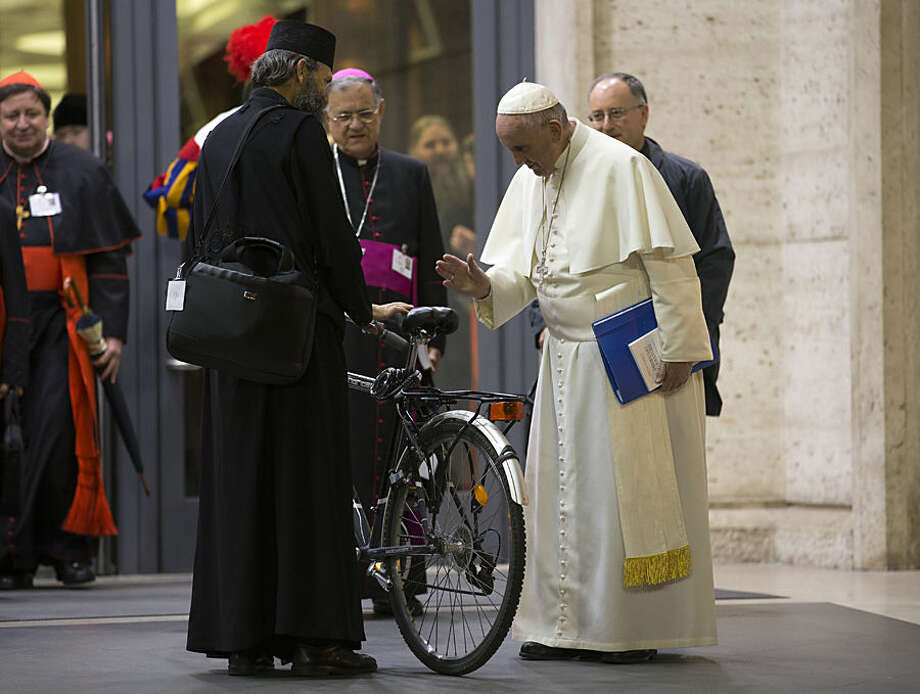 Pope Francis blesses the bicycle of a prelate participating in the Synod, after the afternoon session of the Synod of bishops, at the Vatican, Wednesday, Oct. 14, 2015. Pope Francis asked forgiveness Wednesday for recent scandals that have rocked Rome and the Vatican, showing again he doesn't much care about making waves if it's for the sake of reassuring his flock. (AP Photo/Andrew Medichini)