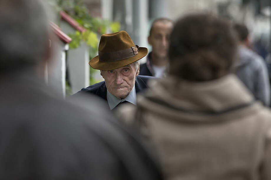 Former communist prison commander Alexandru Visinescu walks away after his appeal at the High Court for Cassation and Justice in Bucharest, Romania, Wednesday, Oct. 14, 2015. Visinescu, commander of the Ramnicu Sarat prison from 1956 to 1963, was convicted, in the first such trial in Romania, to 20 years in jail for the deaths of 12 political prisoners during his command. The hearing was quickly adjourned because Visinescu did not have a lawyer. (AP Photo/Vadim Ghirda)