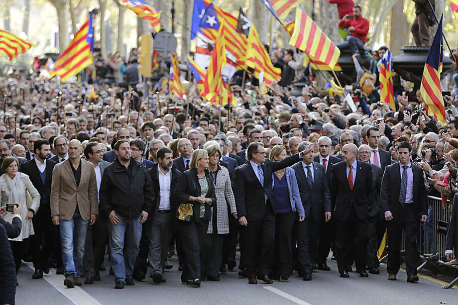 Regional acting President Artur Mas, center, waves to the crowd as he arrives at the Catalonia's high court for questioning over their suspected roll in holding a poll in Barcelona, Spain, Thursday, Oct. 15, 2015. Thousands of people are rallying outside a Barcelona court in support of Catalan regional acting President Artur Mas who has arrived for questioning over the staging of a symbolic referendum on secession from Spain last year. (AP Photo/Emilio Morenatti)
