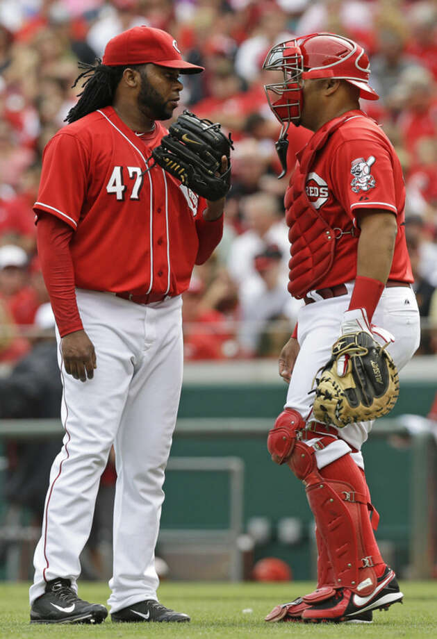 Cincinnati Reds starting pitcher Johnny Cueto, left, talks with catcher Brayan Pena, right, in the first inning of a baseball game against the New York Mets, Saturday, Sept. 6, 2014, in Cincinnati. (AP Photo/Al Behrman)