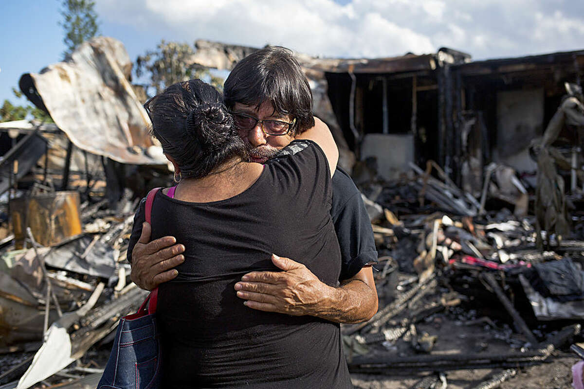 Domingo Galicia, right, embraces a friend as he stands in the rubble of his home the day after a small plane crashed into the residence killing his daughter, Banny Galicia, 21, who was asleep in her room, at the mobile home park, Wednesday, Oct. 14, 2015, in Palm Springs, Fla. (Brianna Soukup/Palm Beach Post via AP) MAGS OUT; TV OUT; NO SALES; MANDATORY CREDIT