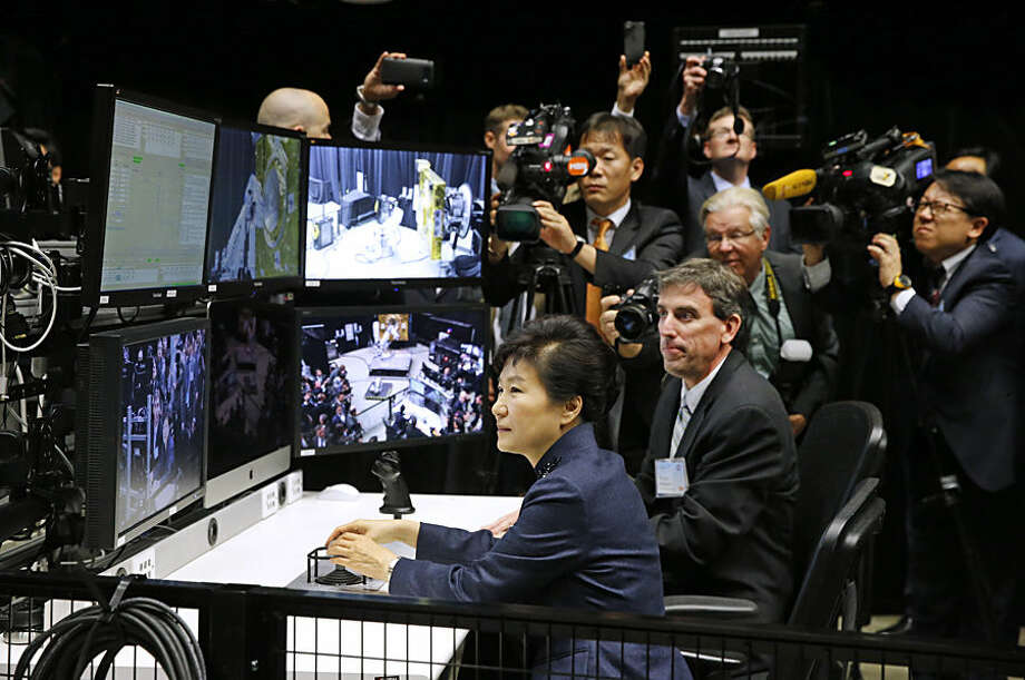 South Korean President Park Geun-hye, bottom center, operates a robotic arm alongside robotic operations manager Brian Roberts during a tour of projects and programs that are underway at the agency's Goddard Space Flight Center, Wednesday, Oct. 14, 2015, in Greenbelt, Md. (AP Photo/Patrick Semansky)