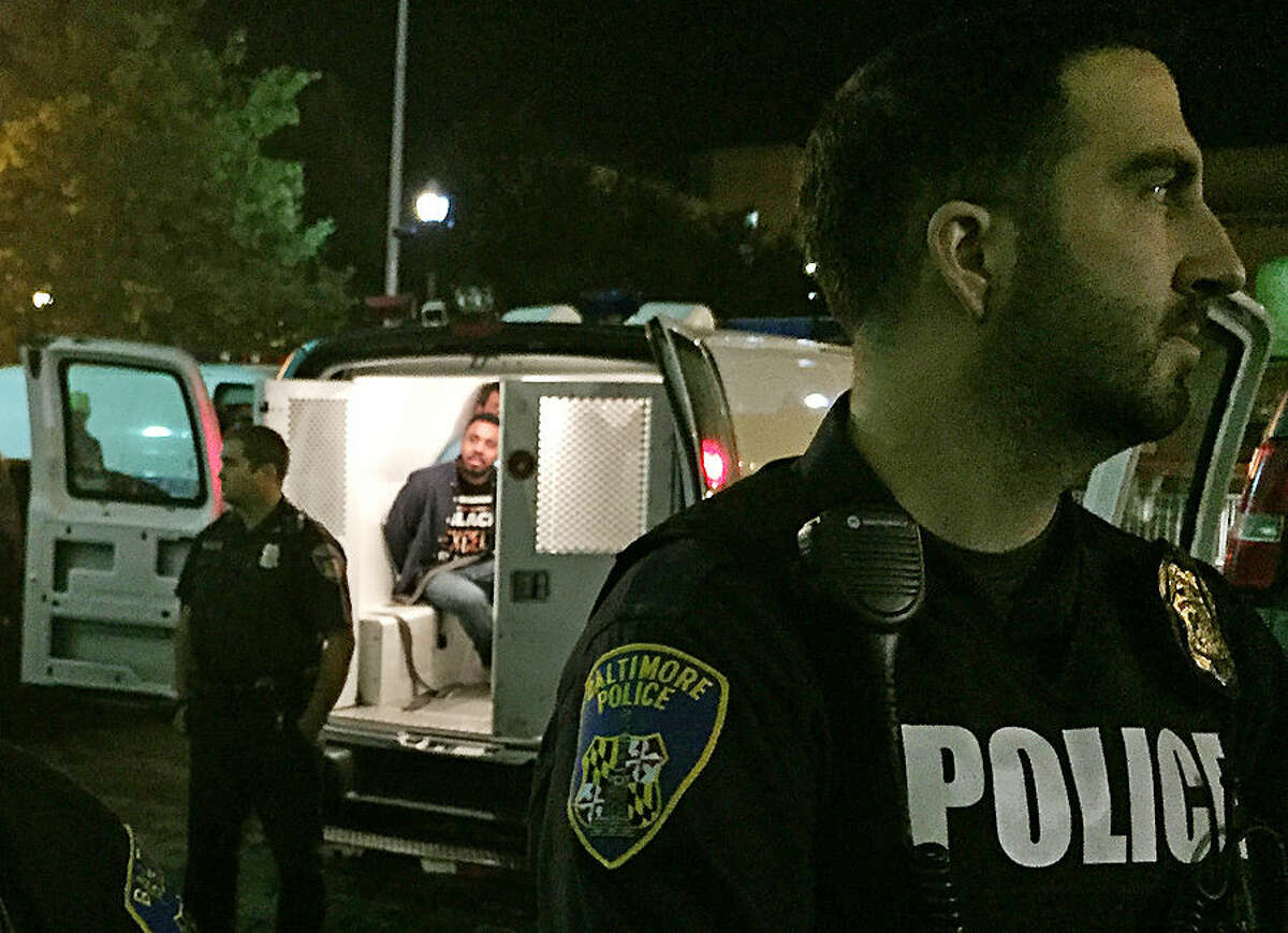 Police stand near vans holding protesters early Thursday, Oct. 15, 2015, in Baltimore. The Baltimore Uprising coalition had occupied City Council chambers at city hall to pretest a council subcommittee's vote in favor of making the interim police commissioner permanent. Police led protesters to vans and other vehicles. (AP Photo/Juliet Linderman)