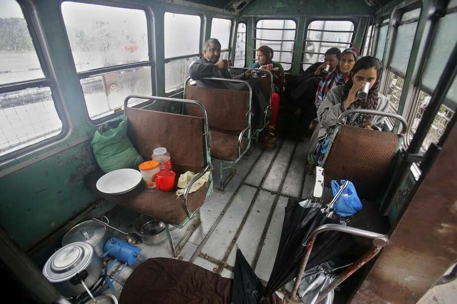 Kashmiris drink tea inside a bus where they have taken shelter after their homes were inundated by floodwaters in Srinagar, India, Saturday, Sept. 6, 2014. Heavy monsoon rains have caused flash floods and landslides that left more than 100 people dead in the disputed Himalayan region of Kashmir and in eastern Pakistan, officials said Friday. (AP Photo/Mukhtar Khan)