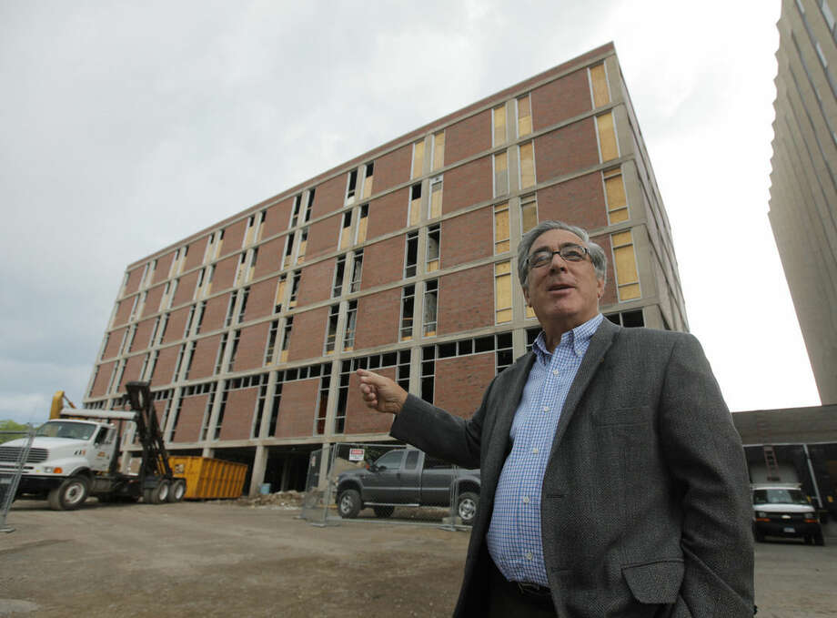 In this June 24, 2010 photo, developer Larry Glazer gestures toward a building to be demolished on Alexander Street in Rochester, N.Y. Glazer and wife, Jane, were aboard their small plane, which took off from the Greater Rochester International Airport, as it flew 1,700 miles down the East Coast on Friday, Sept. 5, 2014, before finally crashing off the coast of Jamaica. (AP Photo/Democrat & Chronicle, Carlos Ortiz) MAGS OUT; NO SALES
