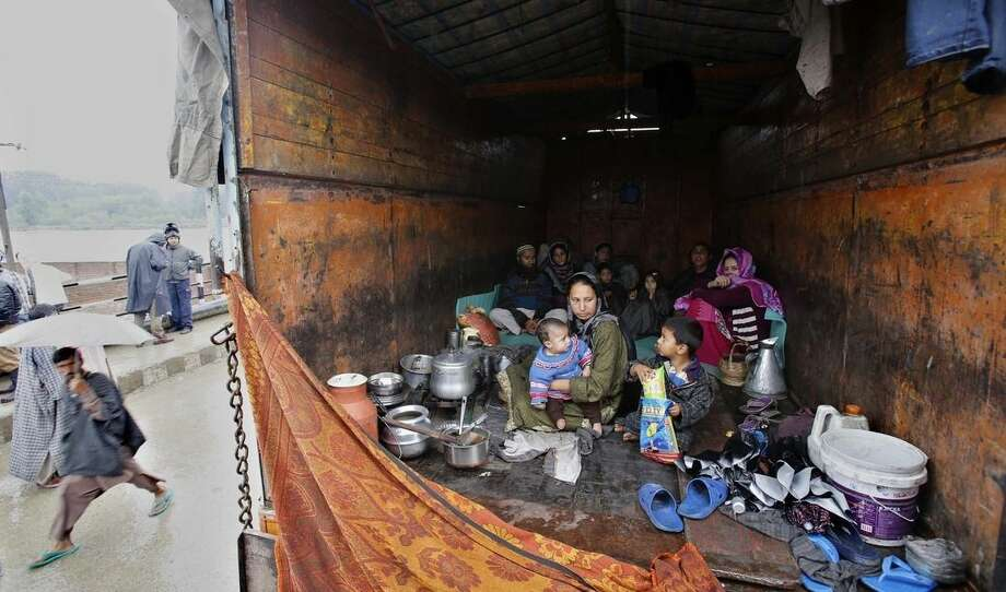 A Kashmiri family takes shelter inside a truck after their home was inundated by floodwaters in Srinagar, India, Saturday, Sept. 6, 2014. Heavy monsoon rains have caused flash floods and landslides that left more than 100 people dead in the disputed Himalayan region of Kashmir and in eastern Pakistan, officials said Friday. (AP Photo/Mukhtar Khan)