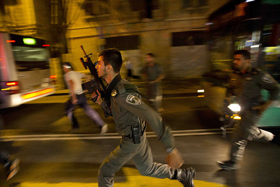 Israeli policemen run looking for a possible stabbing suspect in Jerusalem, Wednesday, Oct. 14, 2015. An Israeli woman was stabbed by an Arab and attacker was shot, the police spokesman said. (AP Photo/Dusan Vranic)