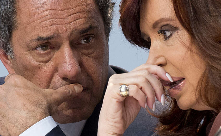 Ruling party presidential candidate Daniel Scioli, left, and Argentina's President Cristina Fernandez talk during the presentation of a new line of products at a L'Oreal cosmetics factory in Buenos Aires, Argentina, Wednesday, Oct. 14, 2015. Scioli, who has been the country's vice president and the governor of Buenos Aires province, recently finished first in the open primaries, and will face a run-off election on Oct. 25. Fernandez is barred from seeking a third consecutive term. (AP Photo/Natacha Pisarenko)