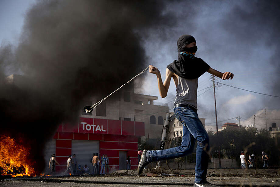 A Palestinian hurls a stone during clashes with Israeli troops near Ramallah, West Bank, Wednesday, Oct. 14, 2015. Violence quickly spread across Israel and into the West Bank and Gaza Strip after clashes erupted last month over tensions regarding the Al-Aqsa Mosque compound in Jerusalem's Old City. Clashes continued Wednesday between Israeli troops and Palestinian protesters in West Bank cities. (AP Photo/Majdi Mohammed)