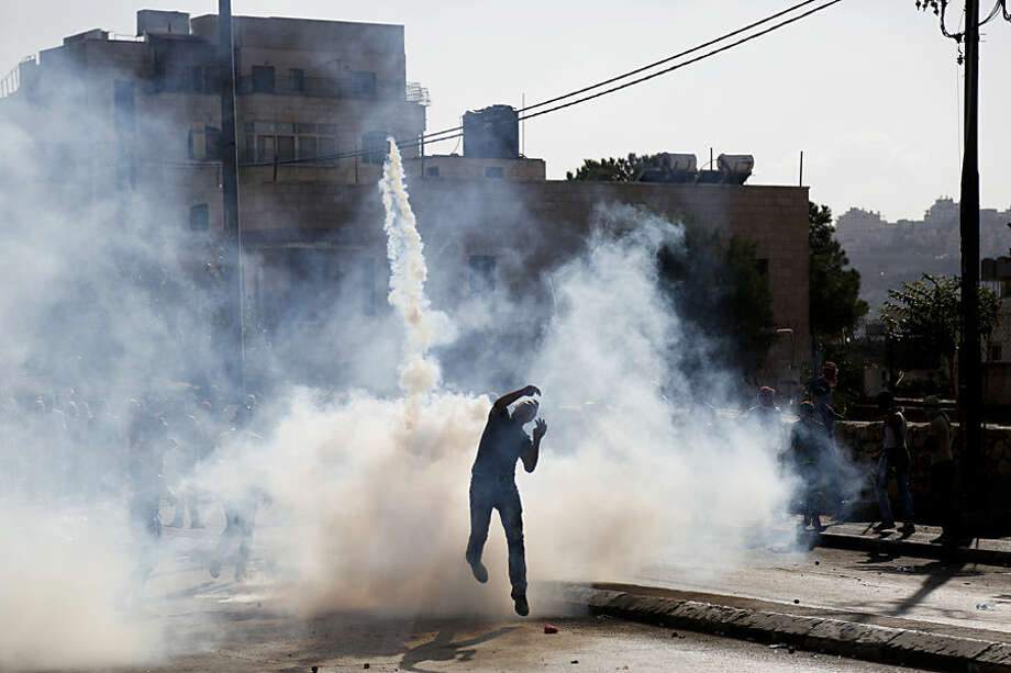 A Palestinian throws back a gear gas canister during clashes with Israeli troops in the West Bank city of Bethlehem on Wednesday , Oct. 14, 2015. The Israeli military began deploying hundreds of troops in cities across the country on Wednesday to assist police forces in countering a wave of deadly Palestinian shooting and stabbing attacks that have created panic across the country. (AP Photo/Nasser Shiyoukhi)