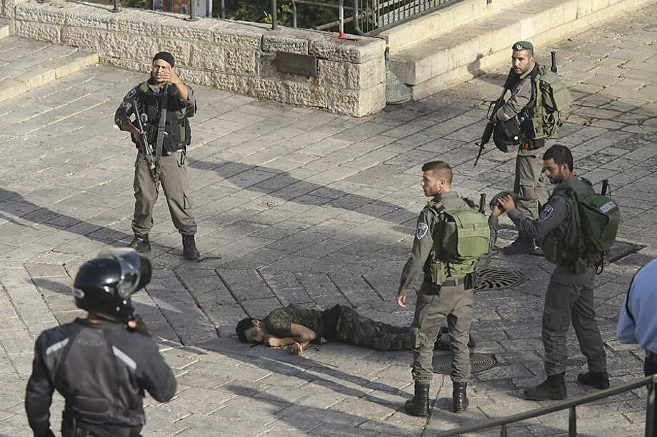 Israeli police stand around a Palestinian shot after he allegedly tried to stab a person at Damascus Gate of the Jerusalem's Old City, Wednesday, Oct. 14, 2015, Israeli police said. (AP Photo/Oren Ziv)