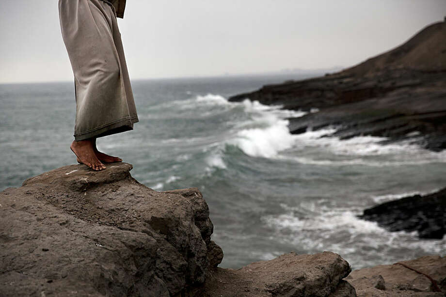 """A performer who reenacts the Monk's Dive or """"El Salto del Fraile,"""" prepares to jump into the Pacific Ocean for clients dining at the restaurant of the same name, in the Chorillos district of Lima, Peru, Wednesday, Oct. 14, 2015. The performer dives daily for tourists and visitors reenacting the legend of the diving monk, who as legend goes, jumped to his death off these neighboring cliffs in despair over an unrequited love. (AP Photo/Rodrigo Abd)."""