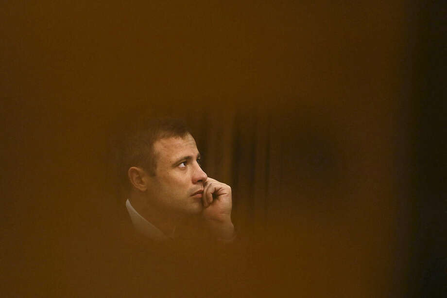 FILE - In this Thursday, Oct. 16, 2014 file photo Oscar Pistorius sits in the high court for the fourth day of sentencing in Pretoria, South Africa. Pistorius is expected to be released Tuesday, Oct. 20, 2015 under house arrest. (AP Photo/Alon Skuy, Pool, File))