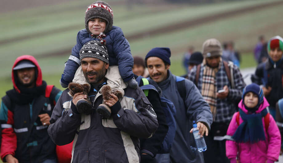 Migrants make their way past meadows and fields to crossthe border between Austria and Germany in Mistlberg, Austria, Thursday, Oct. 15, 2015. (AP Photo/Matthias Schrader)