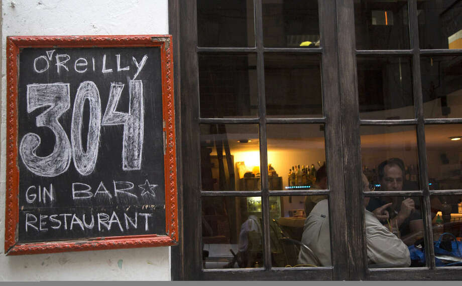 Tourists sit in the popular O´Reilly 304 Bar in Old Havana, Cuba, Tuesday, Oct. 13, 2015. Tour companies showing the Americans around Cuba have sprouted investment consulting arms. Cubans with money and foreign backers are furiously rehabbing old homes into micro-hotels complete with high-end restaurants and conference rooms for business meetings. (AP Photo/Desmond Boylan)