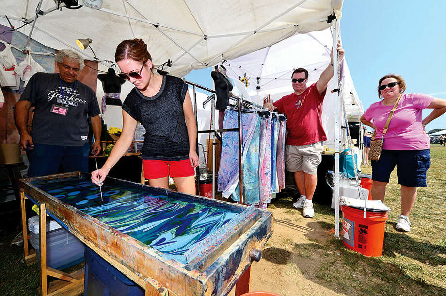 Hour photo / Erik Trautmann Norwalk resident Christine Yoder water marbles a scarf at Shibumi Silk during the Norwalk Seaport Association's 37th annual Oyster Festival at Veteran's Park Saturday.