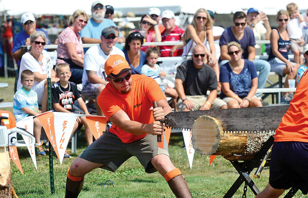 Hour photo / Erik Trautmann Performers with the Paul Bunyan Lumberjack Show saw logs for the audience during the Norwalk Seaport Association's 37th annual Oyster Festival at Veteran's Park Saturday.