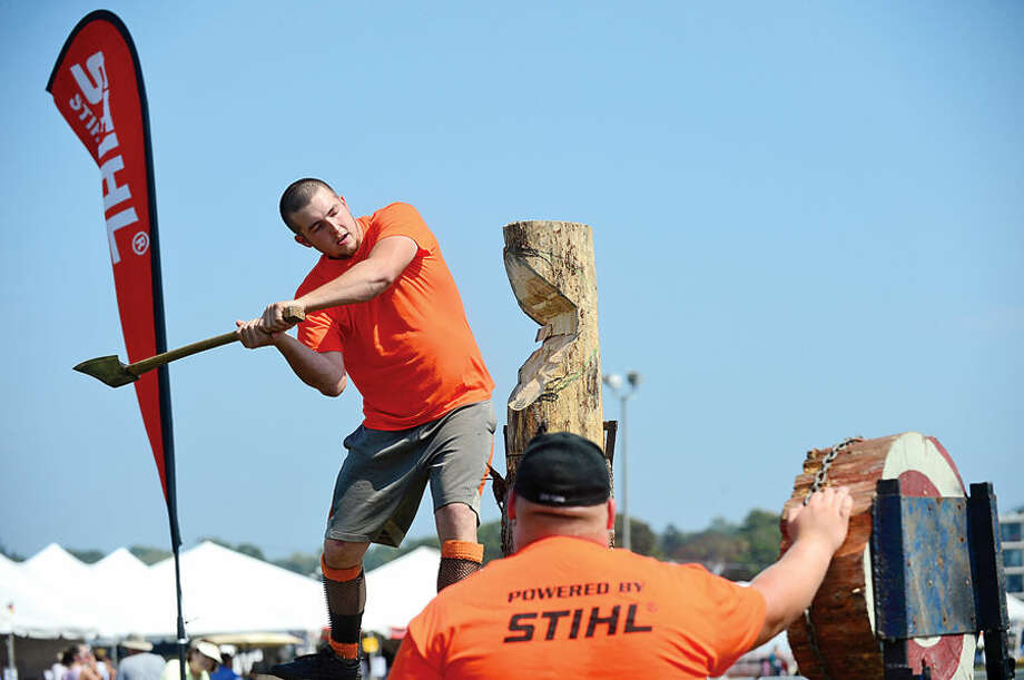 Hour photo / Erik Trautmann Chase Lurdtke, a performer with the Paul Bunyan Lumberjack Show, races to fell a simulated tree during the Norwalk Seaport Association's 37th annual Oyster Festival at Veteran's Park Saturday.